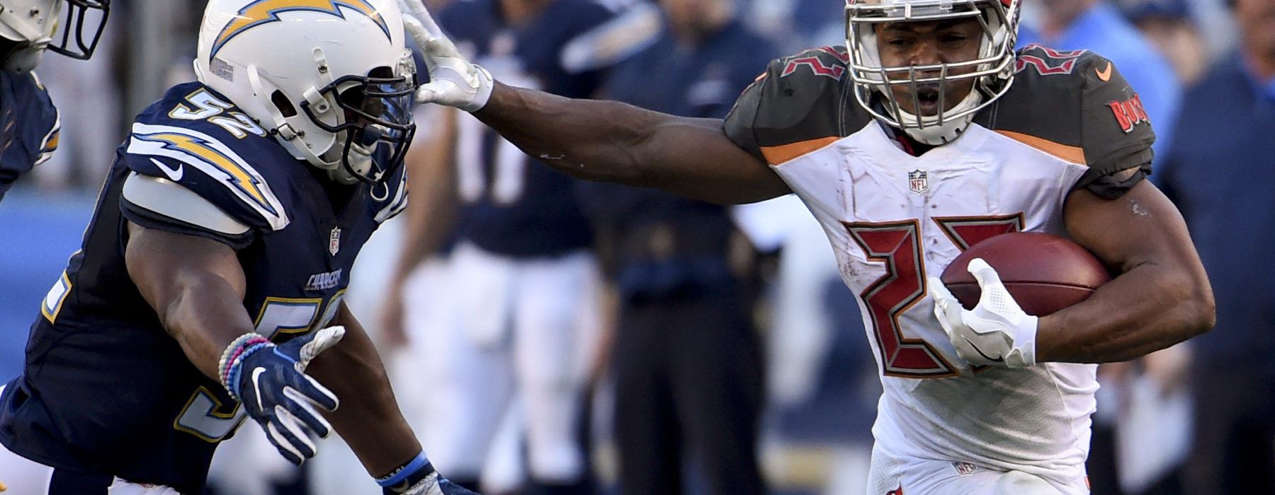 Tampa Bay Buccaneers running back Doug Martin, right, pushes off San Diego Chargers inside linebacker Denzel Perryman during the second half of an NFL football game Sunday, Dec. 4, 2016, in San Diego. (AP Photo/Denis Poroy)